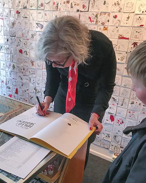 Anna Fiske signerer bøker under utstillingsåpningen